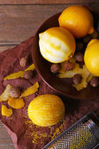 Lemons, nuts and grater on paper on wooden background — Stock Photo