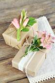 Natural style handcrafted gift boxes with fresh plants and rustic twine, on wooden  — Stock Photo