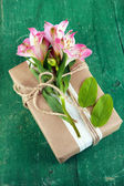 Natural style handcrafted gift box with fresh flowers and rustic twine, on wooden background — Stock Photo