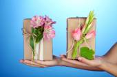 Female hand holding natural style handcrafted gift boxes with fresh flowers and rustic twine, on color background — Stock Photo