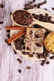 Organic soap with coffee beans, sea salt and milled coffee in wooden spoons on wicker mat, on wooden background, Coffee spa concept — Stock Photo
