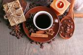 Cup with coffee drink, soap with coffee beans and spices on wooden background. Coffee spa concept — Stock Photo