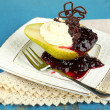 Tasty dessert with pear, cream and berry sauce on plate, on color wooden background — Stock Photo #54514181