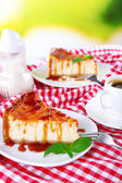 Cheese cake  in plate on red tablecloth on nature background — Stock Photo