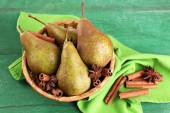 Ripe pears and cinnamon sticks in wicker basket, on color wooden background — Stock Photo