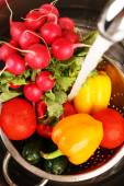 Fresh vegetables in sink in kitchen — Stock Photo