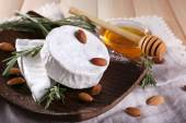 Brie and Camembert cheese with nuts on plate, honey in glass bowl on napkin on wooden background — Stock Photo