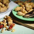 Peanuts and nutcracker on plate, on wooden background — Stock Photo #54521021