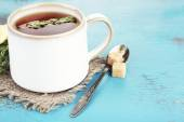 Cup of tasty herbal tea with thyme on blue wooden table — Stock Photo