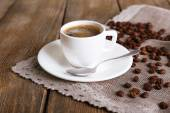 Cup of coffee with milk and coffee beans on napkin on wooden background — Stock Photo
