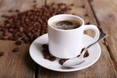 Cup of coffee and coffee beans on napkin on wooden background — Stock Photo