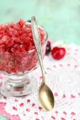 Closeup of cherry granita in glass bowl, on color wooden background — Stock Photo