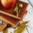 Apple with books and dry leaves on wooden background — Stock Photo #54625729
