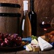 Supper consisting of Camembert and Brie cheese, honey wine and grapes on napkin in basket and wine barrel on wooden table on brown background — Stock Photo #54625961