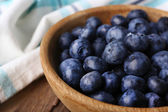 Wooden bowl of blueberries on napkin on wooden background closeup — Stock Photo