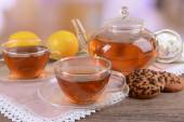 Teapot and cups of tea on table on light background — Stock Photo
