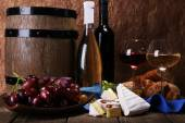 Supper consisting of Camembert and Brie cheese, honey wine and grapes on napkin in basket and wine barrel on wooden table on brown background — Stock Photo