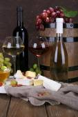 Supper consisting of Camembert and Brie cheese, honey, wine and grapes on sackcloth on stand and wine barrel on wooden table on brown background — Stock Photo