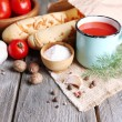 Homemade tomato juice in color mug, bread sticks, spices and fresh tomatoes on wooden background — Stock Photo #54630063