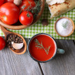 Homemade tomato juice in color mug, bread sticks, spices and fresh tomatoes on wooden background — Stock Photo #54630075