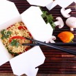 Chinese noodles in takeaway boxes on bamboo mat on wooden background — Stock Photo #54633255