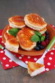 Tasty pancakes with fresh berries, honey and mint leaf on plate, on  wooden background — Stock Photo