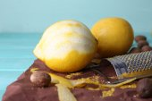 Lemons, nutmegs and grater on paper on blue wooden background — Stock Photo