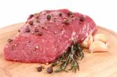 Raw beef meat with spices on wooden cutting board close up — Stock Photo