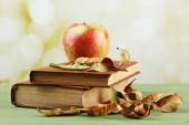 Apple with books and dry leaves — Stock fotografie
