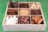 Wooden box with set of coffee and cocoa beans, sugar cubes, dark chocolate, cinnamon and anise over wooden background — Stock Photo