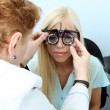 Optometry concept - pretty young woman having her eyes examined by eye doctor — Stock Photo #54839577
