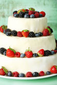 Beautiful wedding cake with berries on color wooden background — Stock Photo