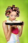 Beautiful girl in hair curlers on green background — Stock Photo