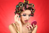 Beautiful girl in hair curlers on red background — Stock Photo