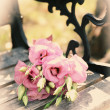Beautiful bouquet of eustoma flowers on wooden bench in park — Stock Photo #54855961