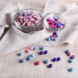Different beads in glass bowls on fabric on table — Stock Photo #54856087