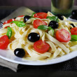 Spaghetti with tomatoes, olives and basil leaves on plate closeup — Stock Photo #54857247