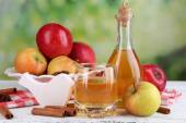 Apple cider  in bottle  with cinnamon sticks and fresh apples on wooden table, on bright background — Stock Photo