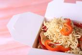 Chinese noodles with meat and pepper in takeaway box on pink background — Stock Photo