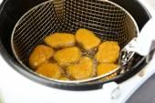 Cutlets in deep fryer — Stock Photo