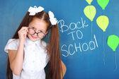 Cute girl standing near blackboard in classroom — Stock Photo