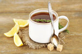 Cup of tasty herbal tea with thyme and lemon on wooden table — Stock Photo