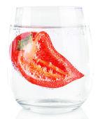 Красный перец в стекле воды, изолированной на белом — Стоковое фото