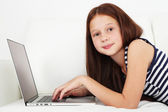 Beautiful little girl with laptop on sofa in room — Stock Photo