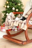 Cute cat on rocking chair in the front of the Christmas tree — Stock fotografie