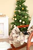 Cute cat on rocking chair in the front of the fireplace — Stock Photo