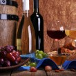 Supper consisting of Camembert and Brie cheese, honey, wine and grapes on napkin in basket and wine barrel on wooden table on brown background — Stock Photo #55019305