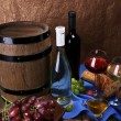 Supper consisting of Camembert and Brie cheese, honey, wine and grapes on napkin in basket and wine barrel on wooden table on brown background — Stock Photo #55019313
