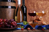 Supper consisting of Camembert and Brie cheese, honey, wine and grapes on napkin in basket and wine barrel on wooden table on brown background — Stock Photo
