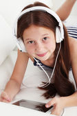 Beautiful little girl listening to music on sofa in room — Fotografia Stock